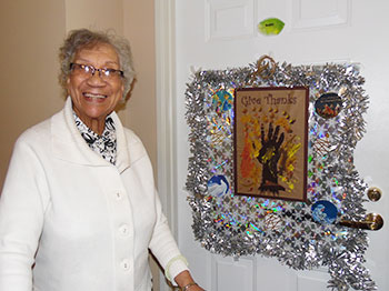 A resident poses in front of a decorated door at Immanuel Courtyard senior living community