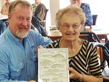 Larry Pape, fishing instruction manager for Nebraska Game and Parks honors Dolores Knispel with a master angler award after a recent fishing trip with fellow Clark Jeary residents through Live Well. Go Fish.