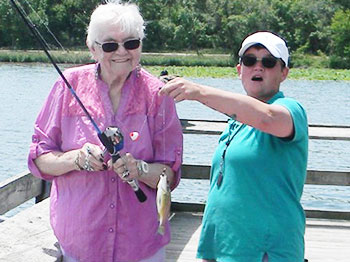 A participant from Immanuel Pathways in Southwest Iowa showcases a catch during a fishing excursion