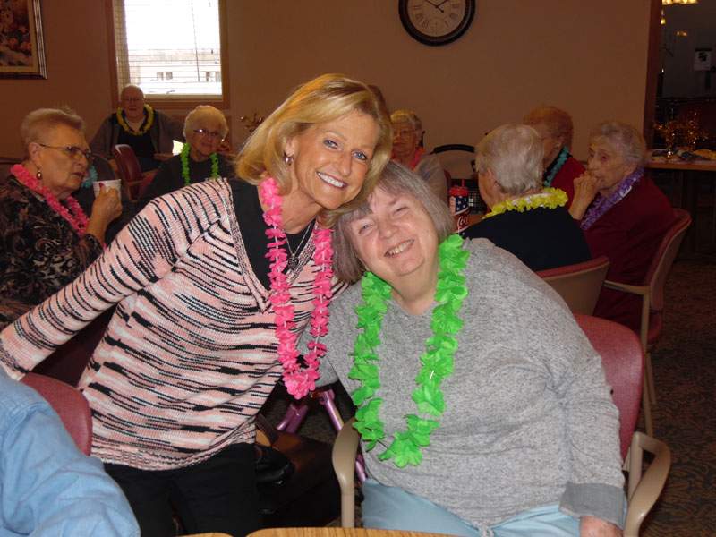 one of the singers from the links poses with an immanuel courtyard resident and their leis