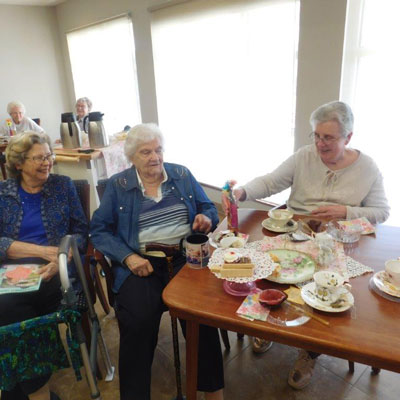 ladies from clark jeary share laughs as they drink their tea