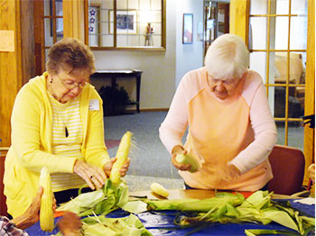 Residents at Immanuel Courtyard shuck corn during a social event at the senior living community.