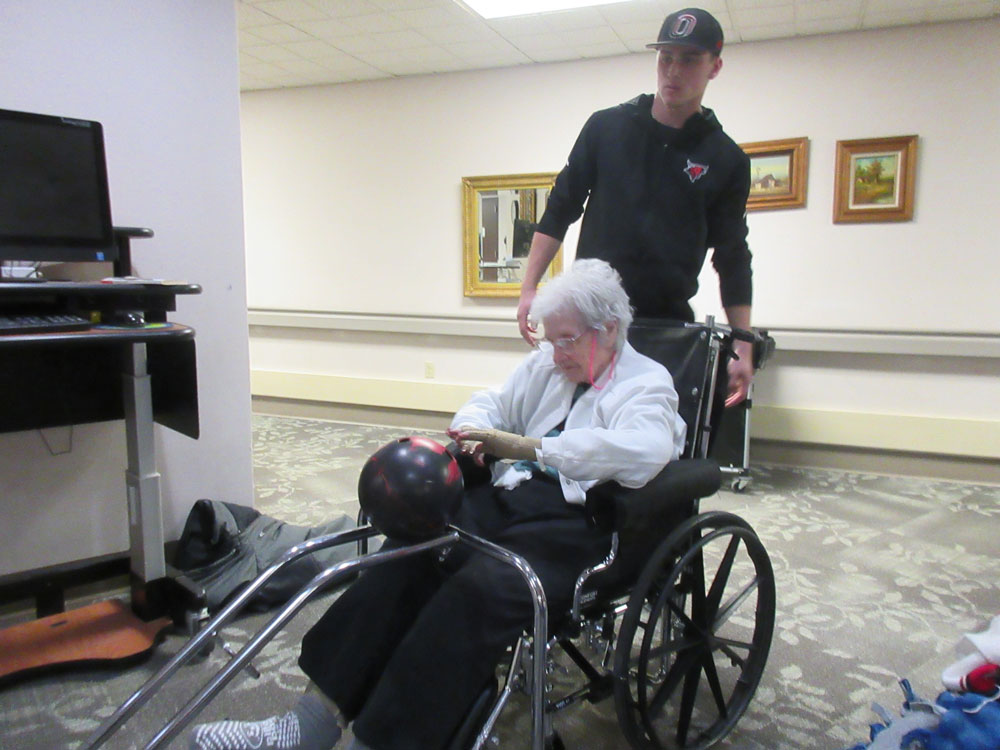 A resident from Immanuel fontenelle senior living community bowls with the help from a UNO Mavericks Baseball player