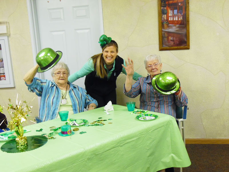 more immanuel courtyard residents wave to the camera with an immanuel courtyard employee dressed in an irish top hat