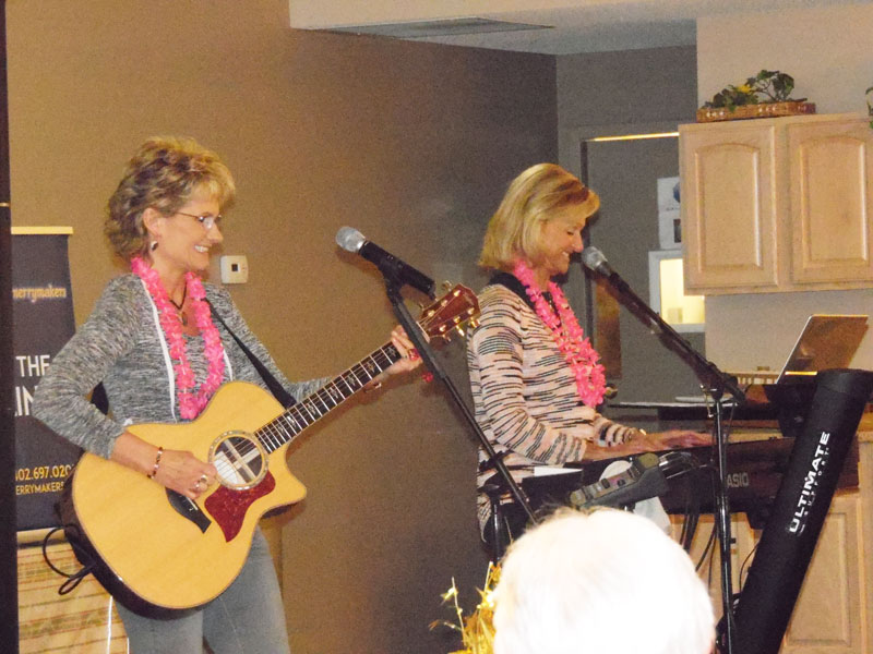 the merrymakers known as the links perform in front of immanuel courtyard residents by singing and playing guitar