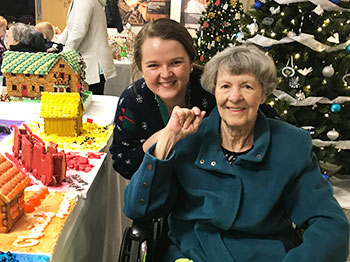 A resident and staff member from Immanuel Fontenelle senior living community enjoys the gingerbread display at the Mormon Trail Center in Omaha, Nebraska