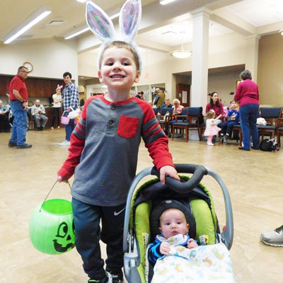 a boy wearing rabbit ears poses with a baby and his easter egg basket