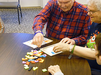 Residents from Pacific Springs Village take part in solving a puzzle during one of their wellness activities