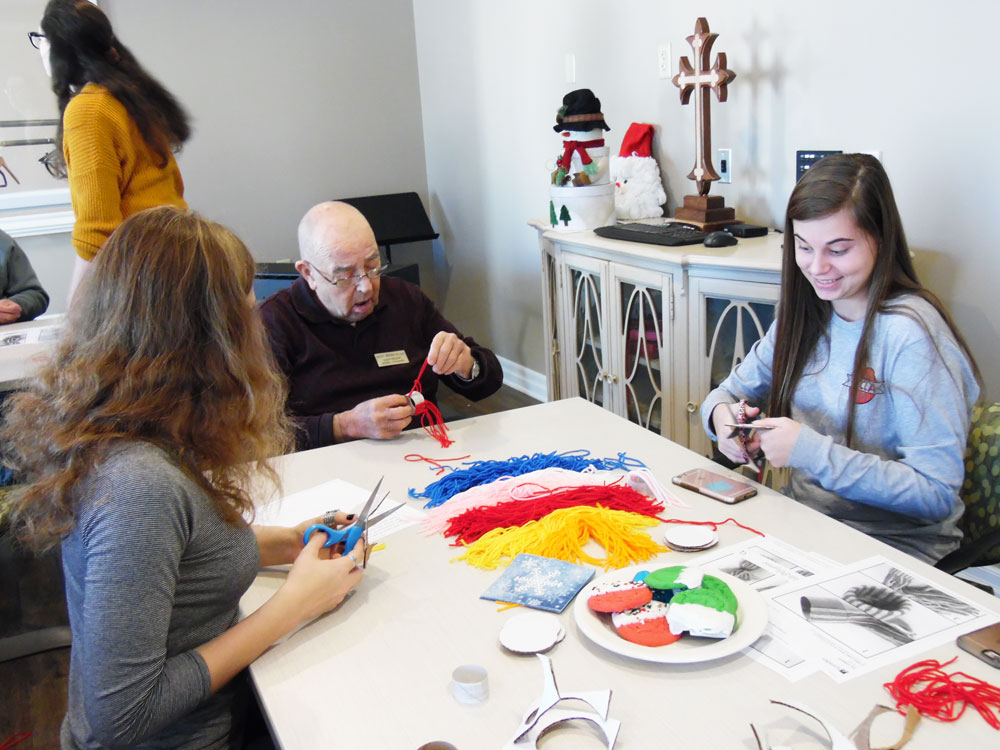 Residents at Pacific Springs Village retirement community make Christmas crafts with Elkhorn High School students