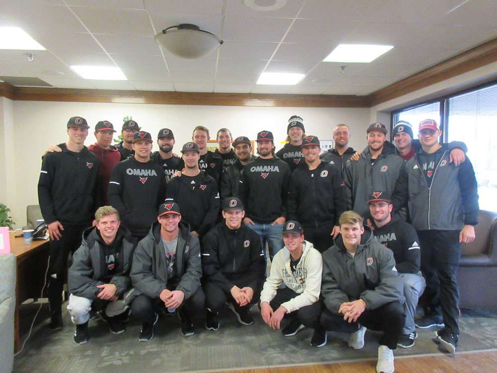 The UNO Mavericks Baseball team poses for a photo at Immanuel Fontenelle during an Athletes and Elders project
