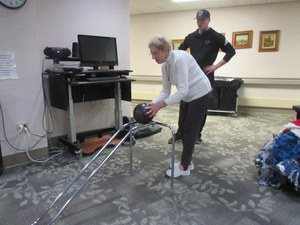 A resident from Immanuel Fontenelle senior living community bowls with the help of a UNO Mavericks baseball player