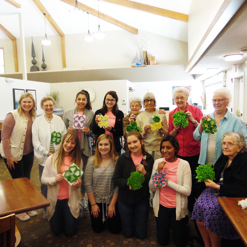 trinity village residents and ladies from the american heart association hold up the four leaf clovers they created during their craft