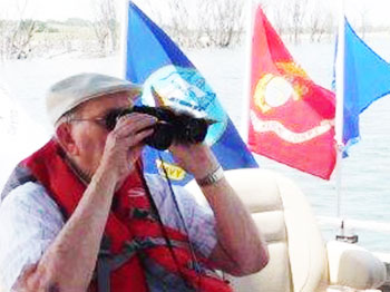 Verne, a resident at Clark Jeary senior living community in Lincoln, Nebraska, looks through his binoculars while floating on a pontoon provided by Live Well. Go Fish., a non-profit organization that arranges fishing trips for seniors and veterans. Verne happens to be a military veteran and was honored by the Live Well. Go Fish crew.
