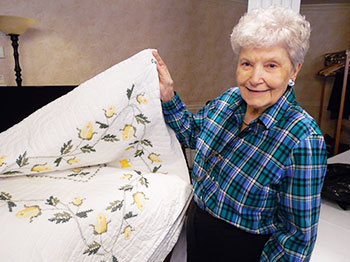 A residents at The Arboretum senior living community showing her handmade quilt at the community's quilt show