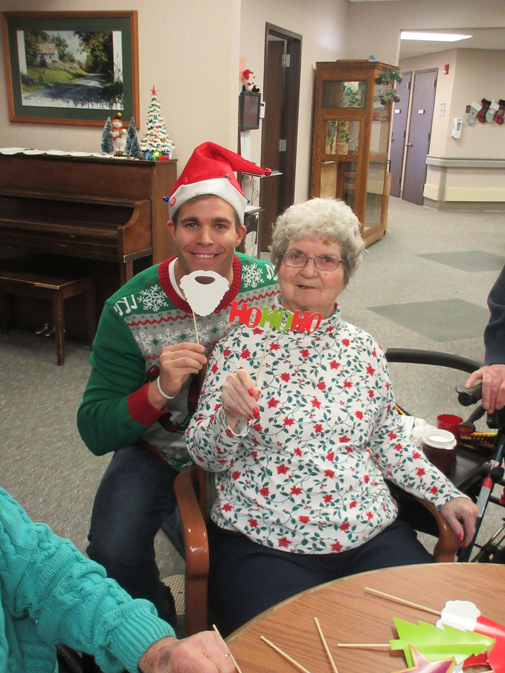 A resident from Immanuel Fontenelle senior living community poses with an employee from Physician's Mutual during a holiday party.