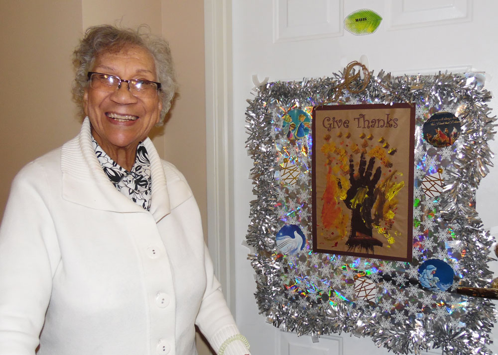 A resident at Immanuel Courtyard senior living community poses in front of her decorated door during the community's festive door contest