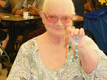 A participant at Immanuel Pathways in Southwest Iowa shows the jewelry that she made during an activity at the center.