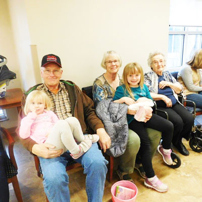 clark jeary residents pose with their granchildren who are holding easter egg baskets
